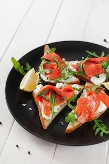 Sanduíche com salmão, queijo, rúcula e limão em um prato preto sobre uma mesa branca