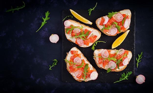 Sanduíche com salmão salgado para café da manhã saudável em superfície escura