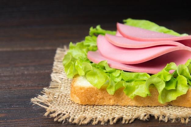 Sanduíche com salsicha fatiada na mesa de madeira