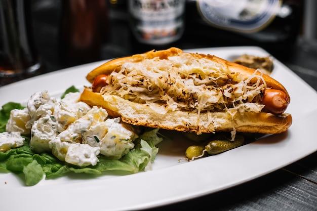 Sanduíche com salsichas grelhadas repolho dentro e salada de batata com creme de leite e verduras alface vista lateral