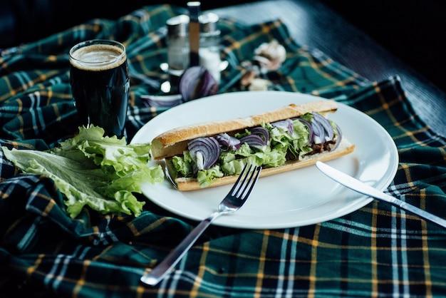 Sanduíche com tomate, cebola e queijo em um prato