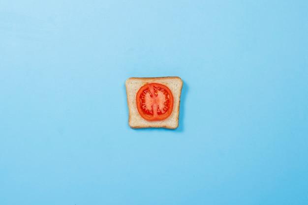 Sanduíche com tomate em uma superfície azul. conceito de dieta, alimentação saudável, perda de peso. vista plana leiga, superior.