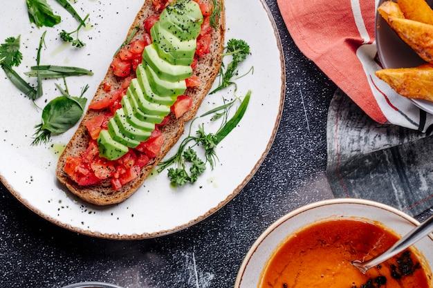 Sanduíche com tomate, pepino e ervas verdes com uma tigela de sopa de lentilha.