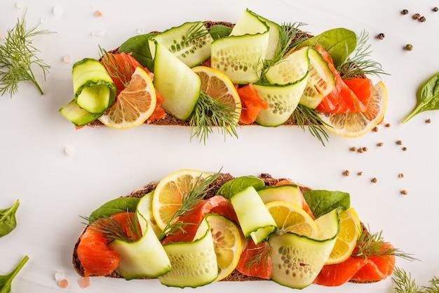 Sanduíche cortado dos peixes da truta (salmões) com ogerets, pão de centeio e aneto no fundo branco.