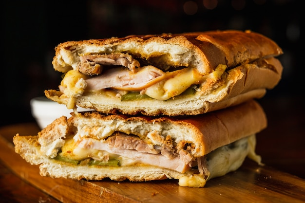 Sanduíche cubano tradicional com queijo, presunto e carne de porco frita, servido em uma placa de madeira