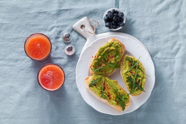 Sanduíche de abacate e rúcula com páprica em cima da mesa. saudável café da manhã ou lanche em um prato numa toalha de mesa de linho azul e suco de laranja espremido na hora