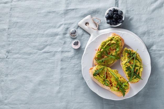 Sanduíche de abacate e rúcula com páprica em cima da mesa. saudável café da manhã ou lanche em um prato numa toalha de mesa de linho azul