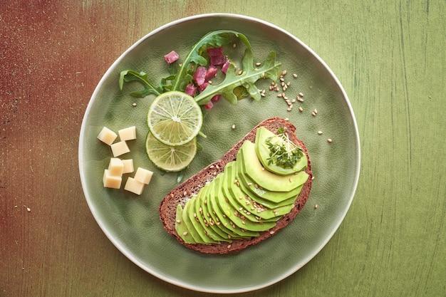 Sanduíche de abacate e salada verde com cubos de presunto na textura marrom-verde