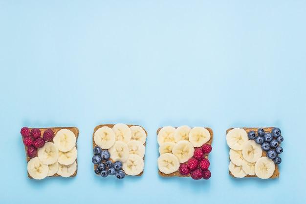 Sanduíche de almoço vegetariano com manteiga de amendoim, banana, framboesa e mirtilo