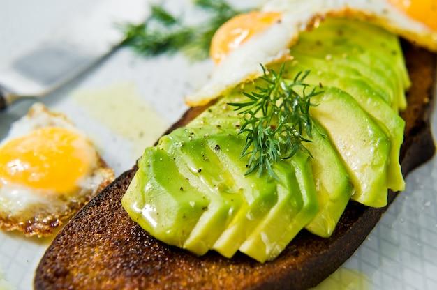 Sanduíche de avacado com ovo no brinde do pão preto.