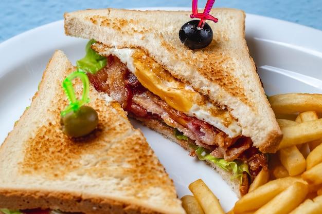 Sanduíche de bacon de vista lateral com bacon frito alface pão torradas azeitonas pretas e verdes batatas fritas num prato
