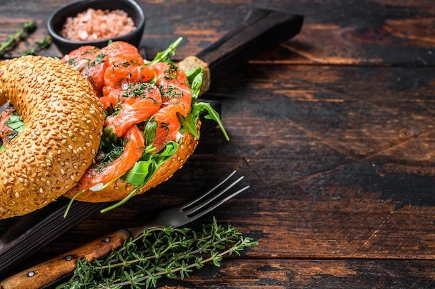 Sanduíche de bagels com salmão e rúcula. fundo de madeira escuro. vista do topo. copie o espaço.