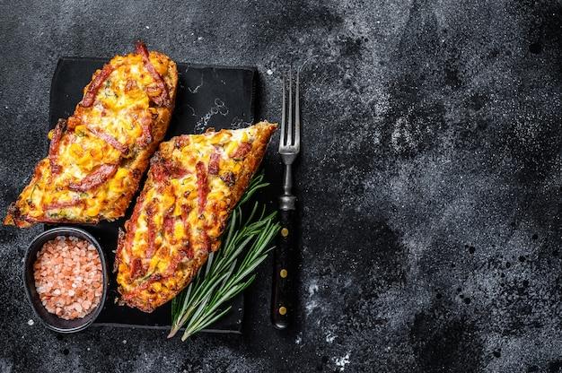 Sanduíche de baguete aberta quente com presunto, bacon, vegetais e queijo