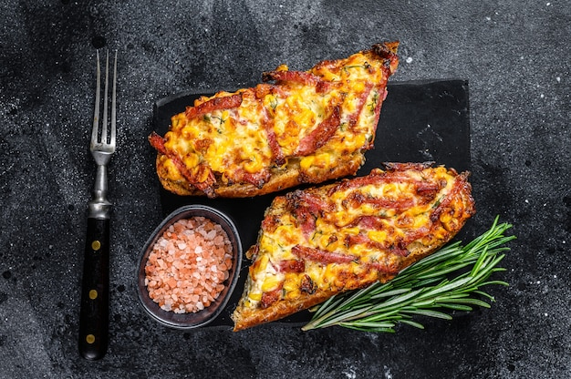 Sanduíche de baguete aberto assado quente com presunto, bacon, legumes e queijo. fundo preto. vista do topo.
