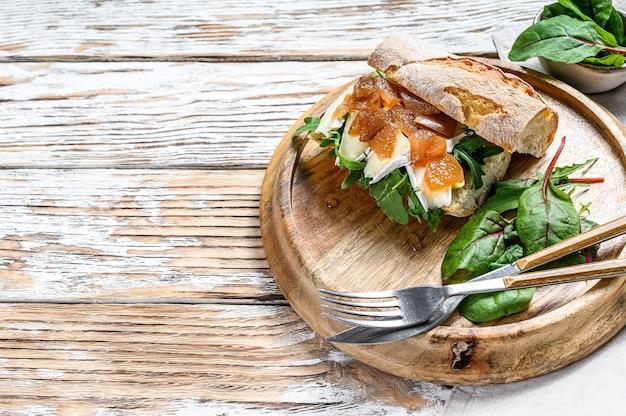Sanduíche de baguete com cream cheese, pêra e acelga. fundo branco. vista do topo. copie o espaço.