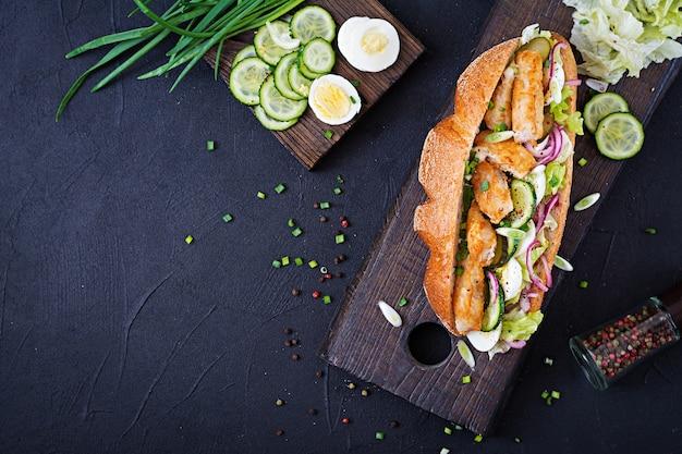 Sanduíche de baguete com peixe, ovo, cebola em conserva e folhas de alface. vista do topo