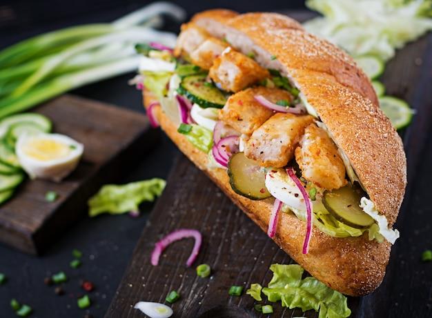 Sanduíche de baguete com peixe, ovo, cebola em conserva e folhas de alface.