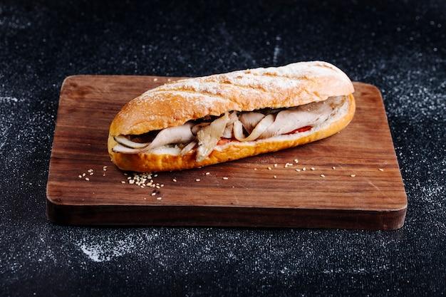 Sanduíche de baguete com presunto em uma placa de madeira.
