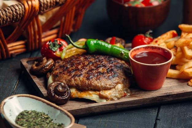 Sanduíche de bife grelhado com queijo e legumes, juntamente com batatas fritas