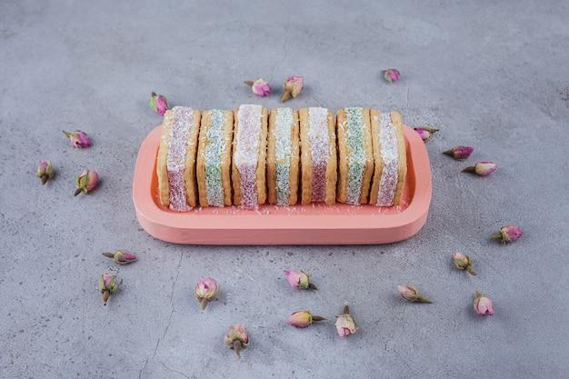 Sanduíche de biscoito cheio de geleia colorida no prato rosa.