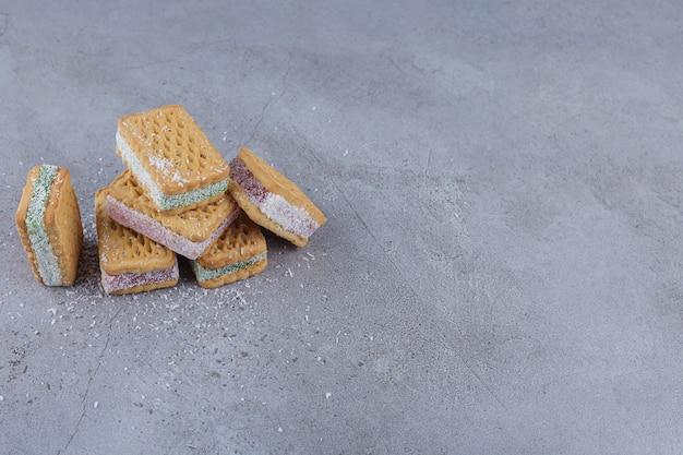 Sanduíche de biscoito cheio de geleia colorida sobre fundo de pedra.