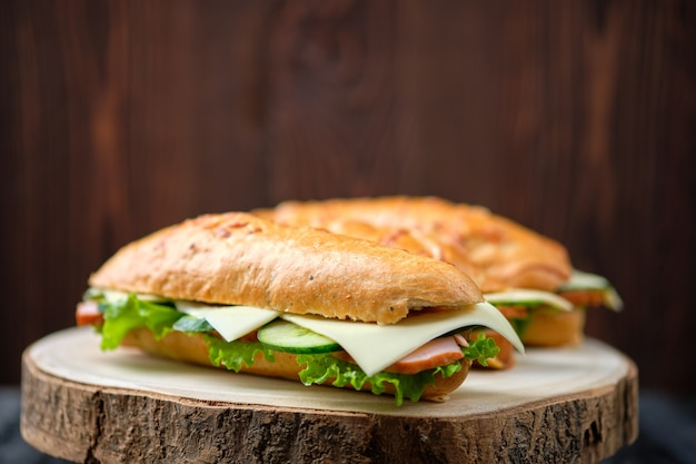 Sanduíche de caçador com presunto, pepino, queijo cheddar na placa de madeira (foto com profundidade de campo)