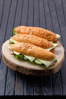 Sanduíche de caçador com presunto, pepino, queijo cheddar na placa de madeira