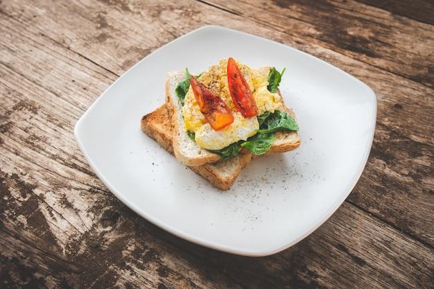 Sanduíche de café da manhã com ovo, agrião e tomate na mesa de madeira, comida saudável