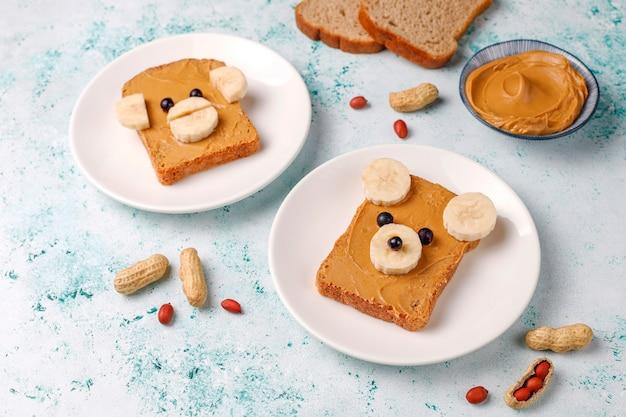 Sanduíche de cara de urso e macaco engraçado com manteiga de amendoim, banana e groselha preta, vista superior