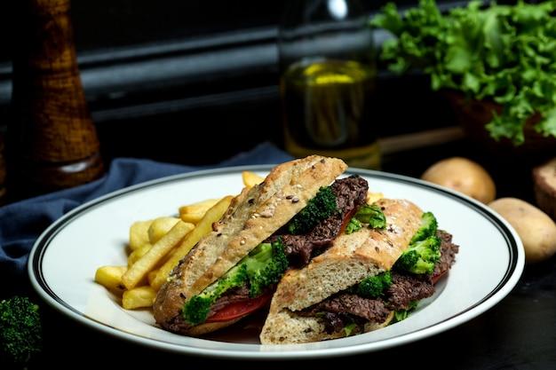 Sanduíche de carne com brócolis, tomate no pão servido com batatas fritas