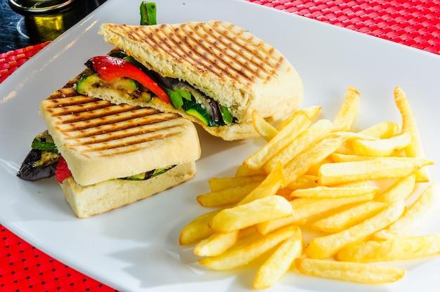 Sanduíche de carne e vegetais servidos com batatas fritas.