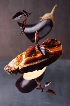 Sanduíche de caviar de berinjela em fundo escuro voando com comida