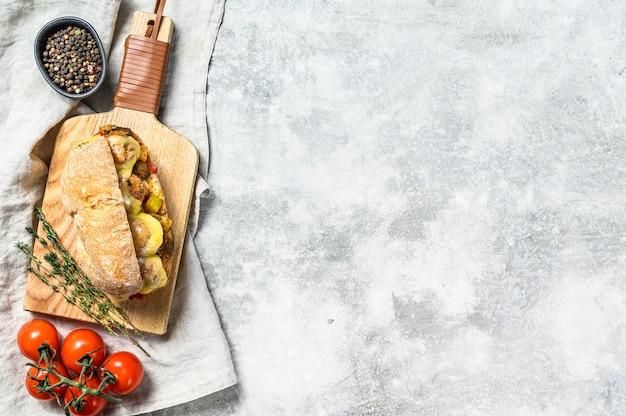 Sanduíche de ciabatta com almôndegas, queijo e molho de tomate. vista do topo. copie o espaço