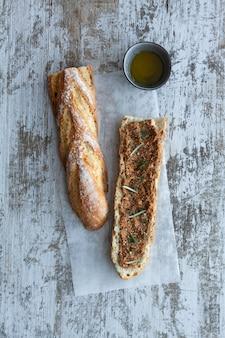 Sanduíche de ciabatta com pesto, ervas, presunto, salame, salsicha, mussarela e espinafre em madeira cinza, vista superior