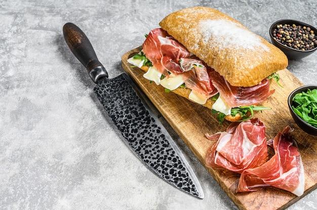 Sanduíche de ciabatta com presunto crudo de presunto, rúcula e queijo brie de camembert. plano de fundo cinza. vista do topo. copie o espaço.