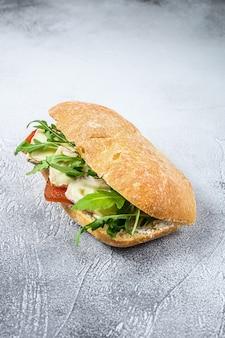 Sanduíche de ciabatta com queijo de cabra fresco, marmelada de pêra e rúcula. fundo cinza. vista do topo. espaço para texto