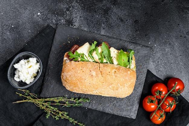 Sanduíche de ciabatta com queijo de cabra fresco, marmelada de pêra e rúcula. fundo preto. vista do topo. espaço para texto