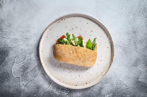 Sanduíche de ciabatta com queijo de cabra fresco, marmelada de pêra e rúcula. superfície cinza. vista do topo