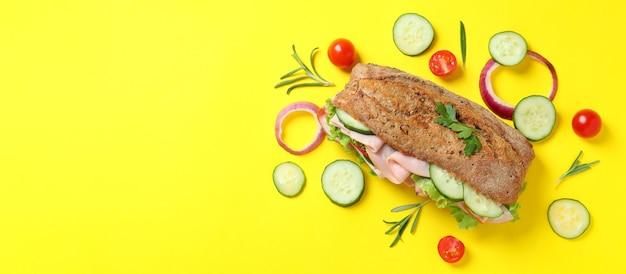 Sanduíche de ciabatta e ingredientes em fundo amarelo