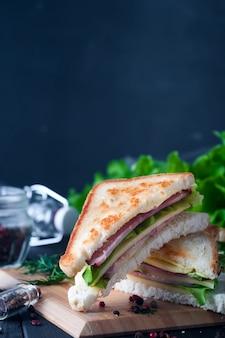 Sanduíche de clube com uma salada na placa de madeira