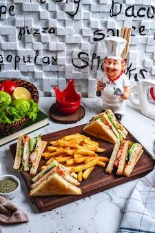 Sanduíche de clube de vista lateral com batatas fritas no quadro