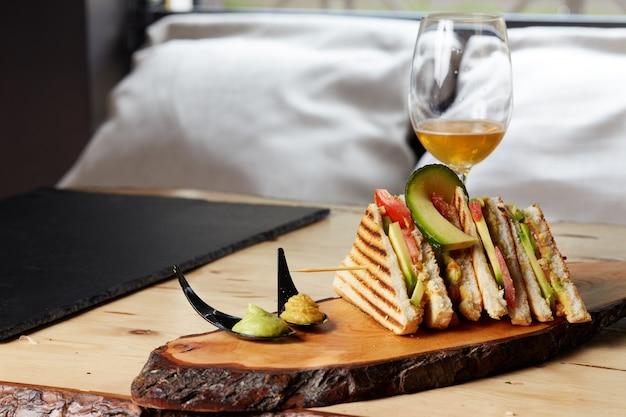 Sanduíche de clube na bandeja de madeira