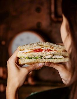 Sanduíche de clube nas mãos da mulher
