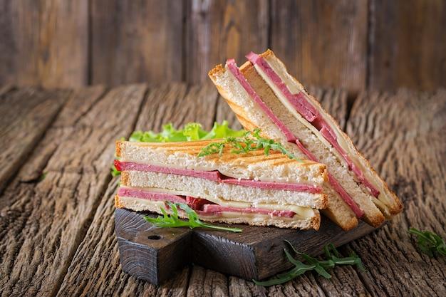 Sanduíche de clube - panini com presunto e queijo na mesa de madeira. comida para piquenique.