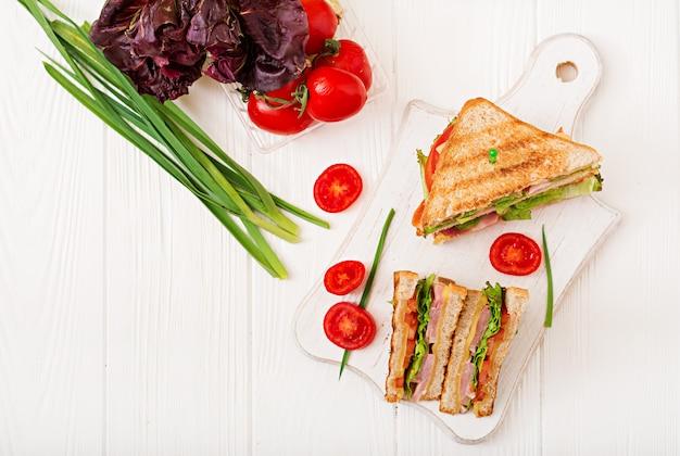 Sanduíche de clube - panini com presunto, queijo, tomate e ervas. vista do topo