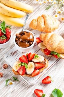 Sanduíche de croissant com banana, chocolate e morango na mesa de madeira