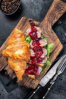 Sanduíche de croissant com fatias de bife de peito de pato, rúcula e molho. fundo preto. vista do topo.