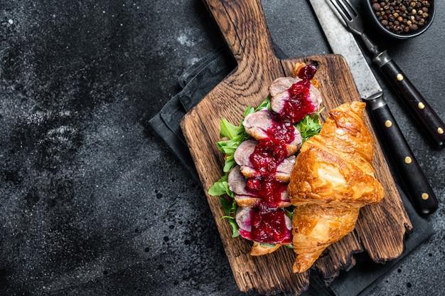 Sanduíche de croissant com fatias de bife de peito de pato, rúcula e molho. mesa preta. vista do topo.