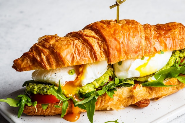 Sanduíche de croissant com ovo escalfado, tomate e guacamole no quadro branco