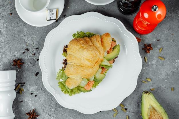 Sanduíche de croissant com peixe vermelho, abacate, legumes frescos e rúcula na placa de xisto preto sobre fundo preto de pedra. conceito de comida saudável.